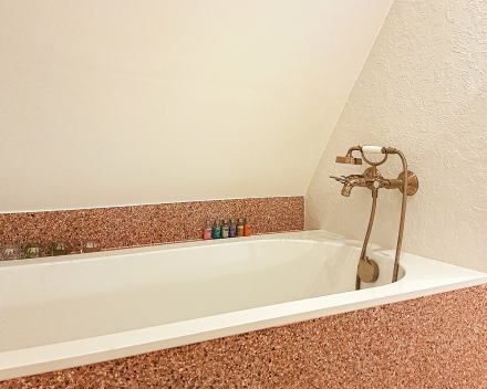 Bad met koperen kraan, koperen douche sproeikop. Zijwanden afgewerkt met kwalitatieve kurk.