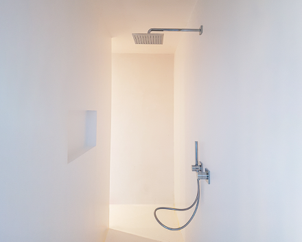 Strakke badkamer renovatie van ingebouwde douche en ingebouwde nis voor het plaatsen van de badkamer producten