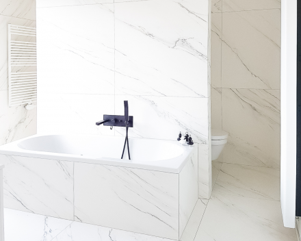 Totaalrenovatie badkamer met bad in marmer gecombineerd met zwarte kraan en zwarte douche sproeier