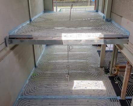 Vloerverwarming op het gelijkvloers als bovenverdieping van een bedrijfsgebouw